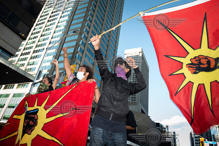 People fly First Nations flags at a rally to defund and abolish the police is held by 'Not Another Black Life', a racial justice organisation.