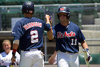 Outfielder Zach Kirksey #11 of the Ole Miss Rebels greets teammate Alex Yarbrough #2 after he scored a run during the NCAA Regional baseball game against the Texas Christian University Horned Frogs on June 1, 2012 at Blue Bell Park in College Station, Texas. Ole Miss defeated TCU 6-2. (Andrew Woolley/Four Seam Images)