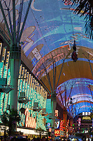 Las Vegas, Nevada.  Fremont Street.  Two Zip Line Riders on the Zoomline Passing Overhead during the Fremont Experience.