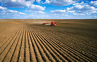 Farm equipment tilling rows in dirt field. Agribusiness. Washington State.