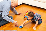Toddler boy age 18 months at home playing with father and toy cars