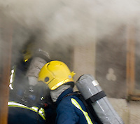 Firefighters wearing Breathing Apparatus going through the front door of a static home to deal with a severe fire. This image may only be used to portray the subject in a positive manner..©shoutpictures.com..john@shoutpictures.com
