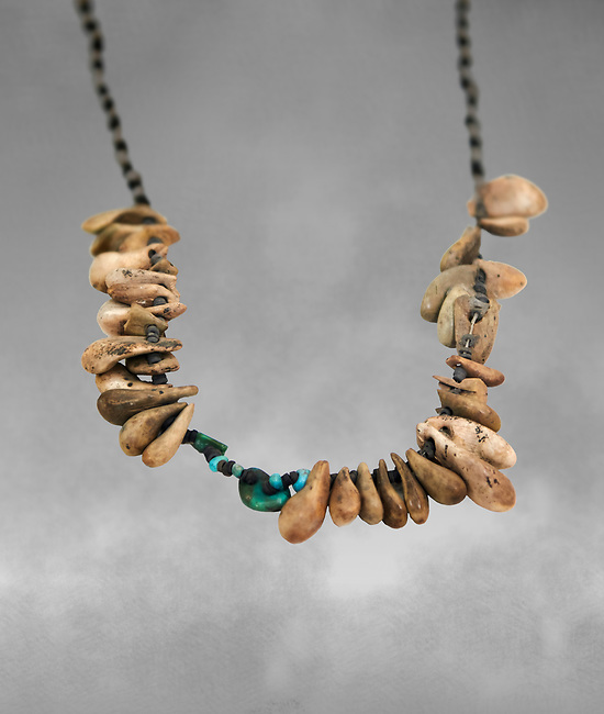 Neolithic necklace, 7000 BC to 6500 BC . Catalhoyuk collection, Konya Archaeological Museum, Turkey. Against a grey background