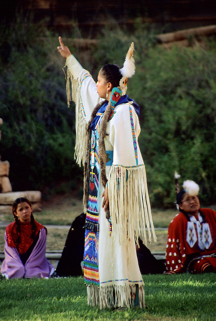 Arapaho teenage girl dressed in traditional deer hide dress with beaded breast plate demonstrates the hand sign language during the national anthem at the Gift of the Waters pageant held in Thermopolis, Wyoming