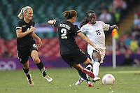 Eniola ALUKO of Great Britain is tackled by Ria PERCIVAL of New Zealand - Great Britain Women vs New Zealand Women - Womens Olympic Football Tournament London 2012 Group E at the Millenium Stadium, Cardiff, Wales - 25/07/12 - MANDATORY CREDIT: Gavin Ellis/SHEKICKS/TGSPHOTO - Self billing applies where appropriate - 0845 094 6026 - contact@tgsphoto.co.uk - NO UNPAID USE.