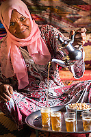 Morocco.  Woman of Arab-Berber Ethnicity Pouring Tea for Guests.  Ait Benhaddou Ksar, a World Heritage Site.