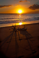 A brilliant sunset drawing long shadows on one of Kauai's beautiful south shore beaches near the town of Waimea.