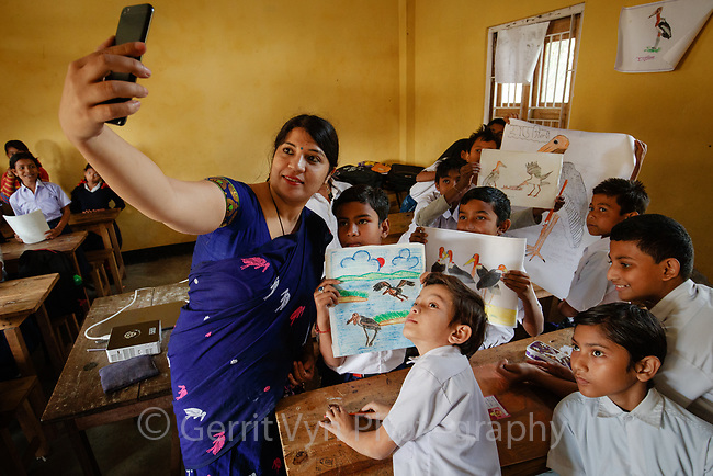 School children being educated about Greater Adjutants that nest in in their village. Dadara, Assam, India. February.