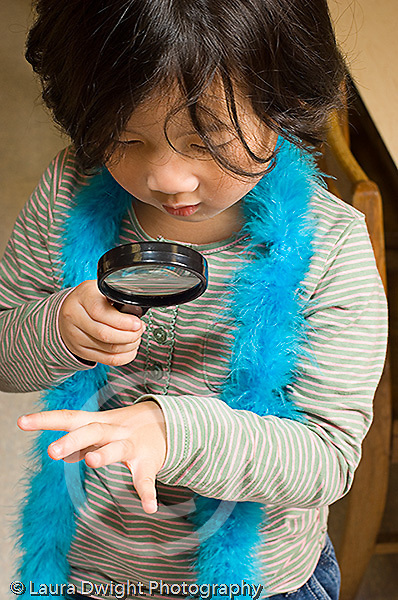 Preschool girl using magnifying glass to look at own hand vertical
