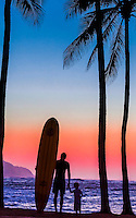 A surfer and his son enjoy the view of Ka'ena Point at sunset, Haleiwa Beach Park, North Shore, O'ahu.