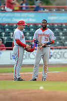 Harrisburg Senators outfielder Brian Goodwin #23 gives his helmet and gloves to coach Eric Fox #28 in between innings during a game against the Erie Seawolves on July 2, 2013 at Jerry Uht Park in Erie, Pennsylvania.  Erie defeated Harrisburg 2-1.  (Mike Janes/Four Seam Images)