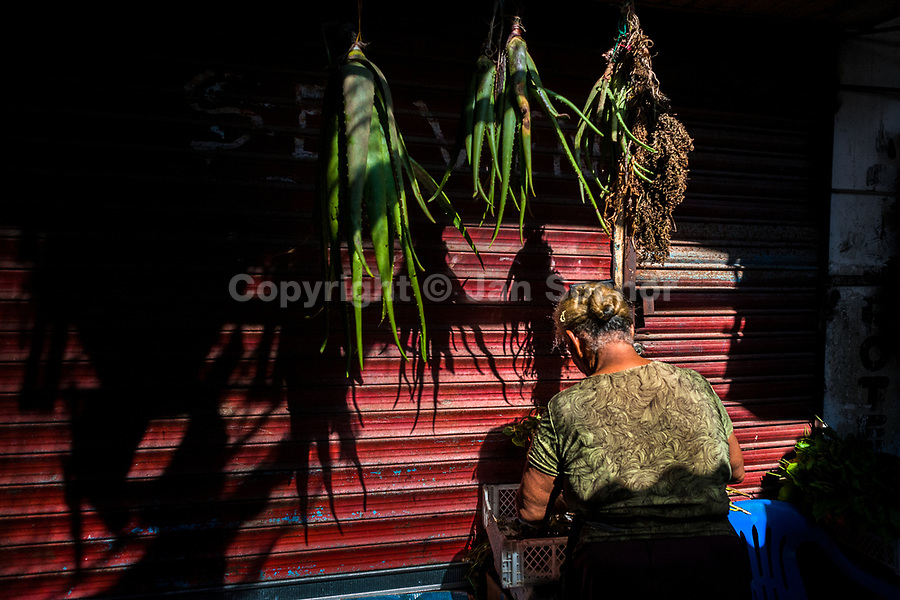 An Afro-Colombian herbs vendor sells aloe vera in the market of Bazurto in Cartagena, Colombia, 14 December 2017. Far from the touristy places in the walled city, a colorful, vibrant labyrinth of Cartagena's biggest open-air market sprawls to the Caribbean seashore. Here, in the dark and narrow alleys, full of scrappy stalls selling fruit, vegetables and herbs, meat and raw fish, with smelly garbage on the floor and loud reggaeton music in the air, the African roots of Colombia are manifested.