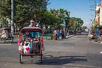 Yogyakarta, Java, Indonesia.  Woman  Riding in a Becak, a Three-wheeled Vehicle Powered by Human Propulsion.  Jalan Malioboro Street.