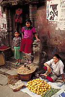 Mother sitting on ground tends produce on towels or in basket; daughters stand on Nara Devi Temple steps; posters on wall. Kathmandu, Nepal.