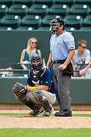 Myrtle Beach Pelicans catcher Patrick Cantwell (3) looks to the dugout for the sign as home plate umpire Jorge Teran looks on during the Carolina League game against the Winston-Salem Dash at BB&T Ballpark on July 7, 2013 in Winston-Salem, North Carolina.  The Pelicans defeated the Dash 4-2 in game one of a double-header.  (Brian Westerholt/Four Seam Images)