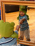 18 month old baby boy in winter hat pointing at his reflection in mirror, recognizing self