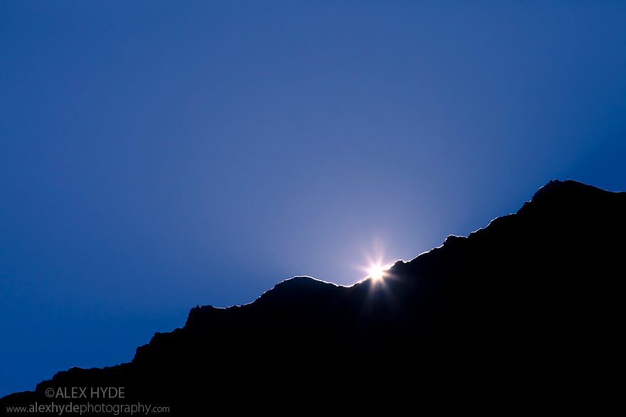 Sun rising over mountain ridge at dawn. French Alps, France.
