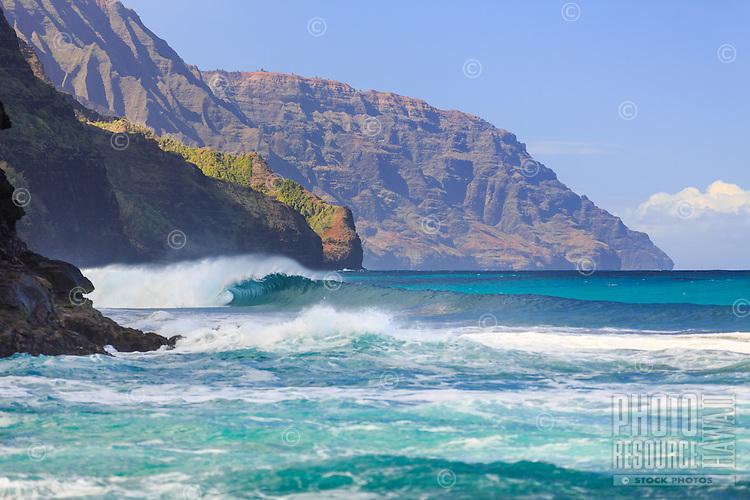 A perfect wave breaks along Kaua'i's misty Na Pali Coast on a sunny day.