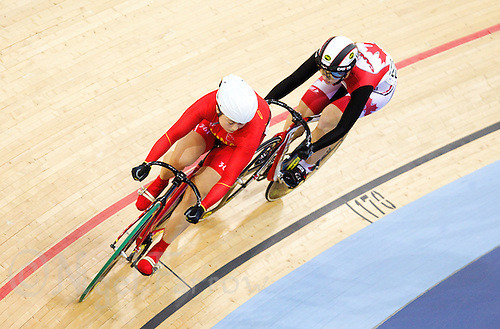 18 FEB 2012 - LONDON, GBR - China's Guo Shuang (CHN) (on the left in red) watches Canada's Monique Sullivan (CAN) (on the right in black, red and white) during their Women's Sprint 1/8 round heat at the UCI Track Cycling World Cup, and London Prepares test event for the 2012 Olympic Games, in the Olympic Park Velodrome in Stratford, London, Great Britain (PHOTO (C) 2012 NIGEL FARROW)