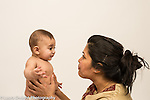 Infant boy age 6 months with mother interaction listening to her make razzing sound with lips