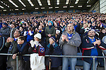 """Portsmouth 1 Southampton 1, 18/12/2012. Fratton Park, Championship. Portsmouth fans in the Fratton End stand at Fratton Park stadium applauding their team on to the pitch before their club take on local rivals Southampton in a Championship fixture. Around 3000 away fans were taken directly to the game in a fleet of buses in a police operation known as the """"coach bubble"""" to avoid the possibility of disorder between rival fans. The match ended in a one-all draw watched by a near capacity crowd of 19,879. Photo by Colin McPherson."""