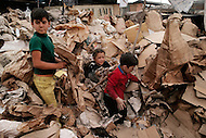 March 1979, Bogota, Colombia - Children sort recycled cardboard outside a garbage dump outside of Bogota. Child labor as seen around the world between 1979 and 1980 - Photographer Jean Pierre Laffont, touched by the suffering of child workers, chronicled their plight in 12 countries over the course of one year.  Laffont was awarded The World Press Award and Madeline Ross Award among many others for his work.