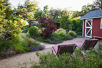 Lounge chairs on gravel bocce ball court with shed secluded from backyard in Habets garden, Pleasant Hill