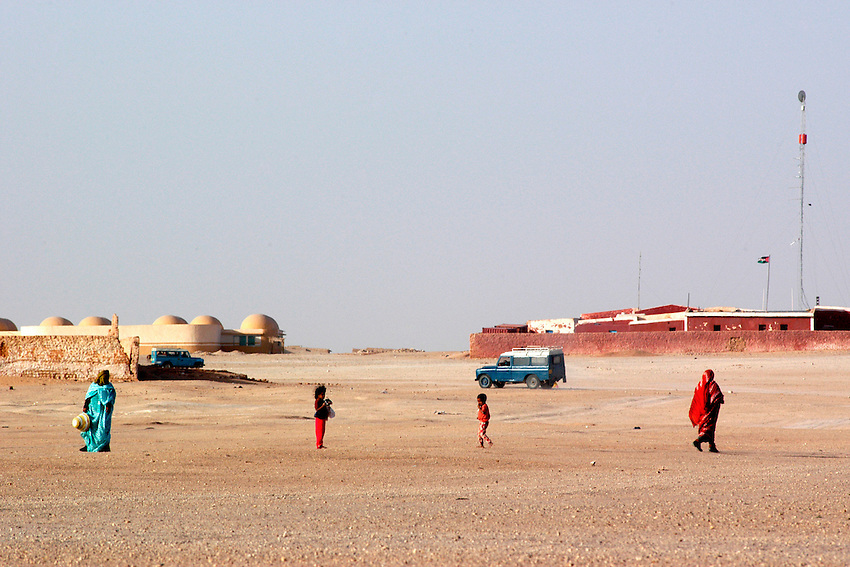 People walk in the Saharawi refugee camps on December 11, 2003. Saharawi people have been living at the refugee camps of the Algerian desert named Hamada, or desert of the deserts, for more than 30 years now. Saharawi people have suffered the consecuences of European colonialism and the war against occupation by Moroccan forces. Polisario and Moroccan Army are in conflict since 1975 when Hassan II, Moroccan King in 1975, sent more than 250.000 civilians and soldiers to colonize the Western Sahara when Spain left the country. Since 1991 they are in a peace process without any outcome so far. (Ander Gillenea / Bostok Photo)