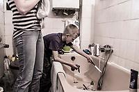 Alleinerziehende mit Kind spuelen im Badezimmer das benutzte Geschirr, Hartz IV, Bochum<br /> <br /> *** HighRes auf Anfrage *** Voe nur nach Ruecksprache mit dem Fotografen *** Sonderhonorar ***<br /> <br /> Engl.: Europe, Germany, Bochum, unemployment benefit, Hartz IV, unemployed, unemployment, poverty, poor, social benefits, single mother, boy, bathroom, washing the dishes, 28 March 2012<br /> <br /> ***Highres on request***publication only after consultation with the photographer***special fee***