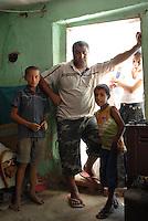 ROMANIA,  Tulcea, 2010/08/24.Family of Ion Ibrisim, in Orizontului street in the suburb of Tulcea, Marla. Houses built illegally without title deed have no water or electricity. Ion thinks one day reach of knowledge in France, in Saint-Denis..© Bruno Cogez / Est&Ost Photography..ROUMANIE, Tulcea, quartier de Marla, 24/08/2010.Famille de Ion Ibrisim, rue Orizontului, dans le quartier périphérique de Marla. Les maisons construites illégalement sans acte de propriété n'ont ni eau ni électricité. Ion pense un jour rejoindre des connaissances en France, à Saint-Denis..© Bruno Cogez / Est&Ost Photography