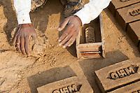 Rajasthan, India.  Man Producing Bricks from Mud Formed by Brick Mold.  Note the Hindu Swastika on the Company Logo.