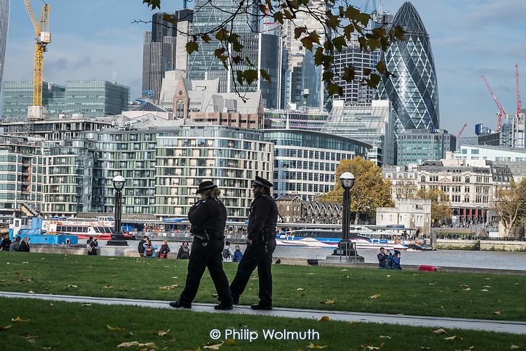 Policing London: police officers  on the South Bank of the river Thames opposite the skyscrapers of the City of London.