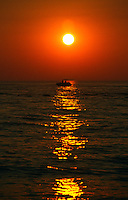 A boat makes its way past the setting sun on Delaware Bay,  off of Cape May, New Jersey.