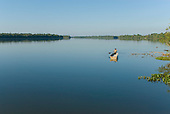 Mato Grosso State, Brazil. Aldeia Metuktire; elder paddling an aluminium voadeira boat on the Xingu River.