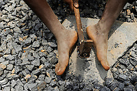 SIERRA LEONE, Freetown, woman works in quarry, smashing granite stones