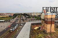 """Andreas Krüger, 42 ans, a installé ses ruches à l'est sur les toits de la mairie de Hellersdorf sur la place Alice Salomon. Marié, deux enfants, il travaille comme éducateur pour dans une institution pour handicapés. Il a commencé l'apiculture il y a six ans pour combler une vieille envie d'enfant et se rapprocher de la nature. «J'avais aussi vraiment envie de faire du miel. J'ai un slogan Du miel plutôt qu'un chien…Ce slogan raconte qu'a Berlin, c'est mieux d'avoir des abeilles qu'un chien car les abeilles y ont un très bon environnement. Autrement, je cours les marathons. J'ai dix ruches et demain, je vais récolter le miel du toit des ruches installées sur le toit de la mairie de Hellersdorf et j'espère avoir 80 kilos par ruches»./// Andreas Krüger, 42 years old, has set up his hives to the east, on the roof of the Hellersdorfer town hall on Alice Salomon square. Married with two children, he works as an instructor in an institution for the handicapped. He started beekeeping six years ago to satisfy an old childhood desire and to get back to nature. """"I also really wanted to make honey. I have a slogan, Honey before dogs…"""" He recounts that in Berlin it's better to have bees than a dog because the bees make it a good environment. """"Otherwise, I run marathons. I have ten hives and tomorrow I am going to harvest the honey from the hives on the Hellersdorfer town hall and I hope to get 80 kilos per hive""""."""