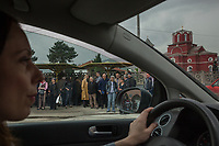 Serbia. Vranje is a city and the administrative center of the Pčinja District in southern Serbia. A woman drives her car and passes by a bus stop. People are waiting at the bus stop. Orthodox church.17.4.2018 © 2018 Didier Ruef for the Pestalozzi Children's Foundation