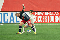 FOXBOROUGH, MA - NOVEMBER 1: Griffin Yow #22 of DC United comes in to tackle Alexander Buttner #28 of New England Revolution during a game between D.C. United and New England Revolution at Gillette Stadium on November 1, 2020 in Foxborough, Massachusetts.