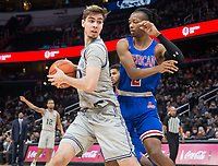 WASHINGTON, DC - DECEMBER 28: George Muresan #20 of Georgetown pulls the ball away from Stacy Beckton JR. #2 of American. during a game between American University and Georgetown University at Capital One Arena on December 28, 2019 in Washington, DC.