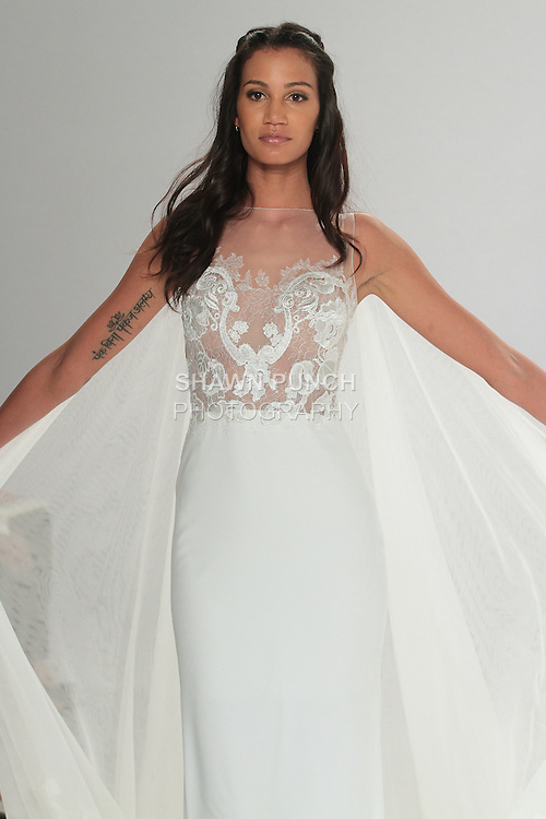 """Model walks runway in Taranis - an off white Georgette sheath dress with a lace bodice and a tulle train embellished with a Guipure hemline, from the Tony Ward Fall 2016 """"A Mid-Summer Night's Dream"""" bridal collection on April 18, 2016 at Kleinfeld Bridal during New York Bridal Fashion Week Spring Summer 2016."""