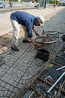 Man repairing the tube tyre of a bicycle on a sidewalk in Datong, Shanxi, China.