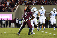 BLACKSBURG, VA - OCTOBER 19: Sam Howell #7 of the University of North Carolina is tackled by Khalil Adler #9 of Virginia Tech during the sixth overtime during a game between North Carolina and Virginia Tech at Lane Stadium on October 19, 2019 in Blacksburg, Virginia.
