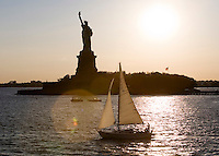 A view of several sailboats in the New York Harbor with the Statue of Liberty in the background.