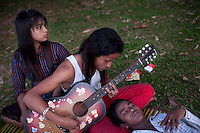 University students relax and play a guitar by a lake in Rangoon (Yangon).