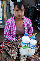 Myanmar, Burma. Woman Selling Grilled Bats in the Bagan Market.  She is wearing thanaka paste on her face, a cosmetic sunscreen.