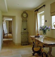 The entrance hall has a new stone tiled floor and is furnished with a Swedish clock and a rustic hall table