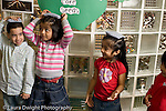 Education Preschool 3-5 year olds circle time activity girls and boy balancing bean bags on their heads horizontal