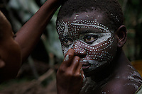 Face painting in deep forest camp.  These folks all had shelter for the night in about two hours.  Women bend the branches to create a superstructures and then go off in the woods to get the right kind of leaves.  The Forest Hunting camps we hiked to are about 10k to the camp and then another 10K to where they string their nets.   Boys who are going thru the end of the circumcision ceremony called Kumbi accompanied the pygmies to the camp and were housed off to the side.  They were whipped every morning and then sent off into the forest to hunt or fish.