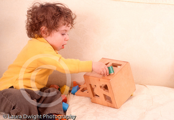 2 year old toddler boy playing with toy shape sorter Caucasian horizontal