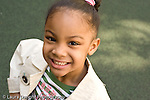 Preschool backyard playground children playing in early spring ages 3-5 New York City closeup portrait of girl smiling happy horizontal